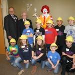 Bill Matthews, President of RMHC of Arkoma Board of Directors; Dick Trammel, Member of RMHC of Arkoma Board of Directors; and Ronald McDonald with children from a local elementary